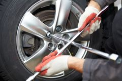 Car mechanic changing tire. Royalty Free Stock Images