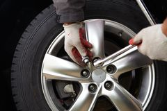 Car mechanic changing tire. Stock Photo