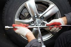Car mechanic changing tire. Car mechanic changing tire in professional car repair service Royalty Free Stock Image