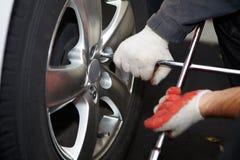 Car mechanic changing tire. Royalty Free Stock Photos