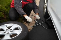Car mechanic changing tire. Royalty Free Stock Photos