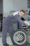 Car mechanic changing tire. Car mechanic changing wheels by tire bead breaker machine Royalty Free Stock Photo