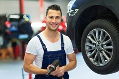 Car mechanic changing tires. In workshop Stock Photo