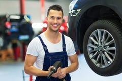Car mechanic changing tires Stock Photo