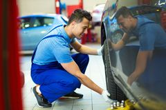 Car mechanic changing tires. In workshop Royalty Free Stock Image