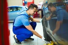 Car mechanic changing tires Royalty Free Stock Image