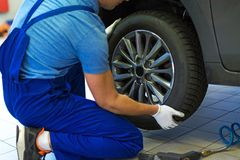 Car mechanic changing tires. In workshop Royalty Free Stock Photo