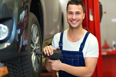 Car mechanic changing tires. In workshop Royalty Free Stock Photography