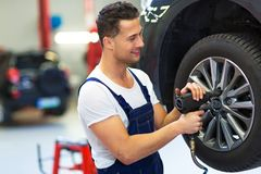 Car mechanic changing tires. In workshop Royalty Free Stock Images