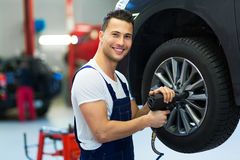 Car mechanic changing tires. In workshop Stock Images