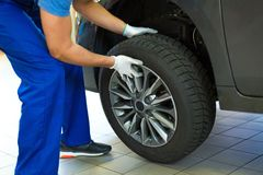 Car mechanic changing tires. In workshop stock image