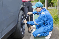 Car mechanic changing a tyre on the road. Young male mechanic wearing uniform, changing a car tyre with his client on the road stock image