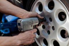 Car mechanic changing wheel Royalty Free Stock Images