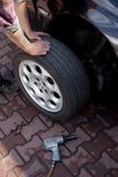 Car mechanic changing wheel Stock Photos