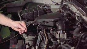 Car mechanic checking the car engine oil and air filter inspection for troubleshooting and repair in the garage or car repair shop stock footage