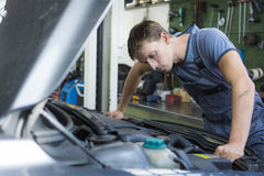 Car mechanic. A car mechanic checking a car engine stock image