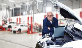 Car mechanic. Car mechanic checking engine. Auto repair service Royalty Free Stock Photo
