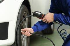 Car mechanic checking tires air pressure. Close up of a car mechanic hands checking tire air with a pressure gauge Stock Image