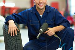 Car mechanic crouching down by a tire Royalty Free Stock Image
