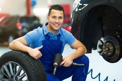 Car mechanic crouching down by a tire Stock Photo