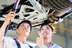 Car mechanic and customer in Asian auto workshop. Asian Chinese car mechanic with customer looking at auto floor with lamp Royalty Free Stock Images