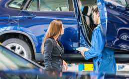 Car Mechanic With Customer Going Through Maintenance Checklist Royalty Free Stock Image