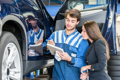 Car Mechanic With Customer Going Through Maintenance Checklist. Car mechanic with female customer going through maintenance checklist in garage Stock Photo