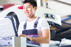 Car mechanic with diagnosis tool in Asian auto workshop. Asian Chinese car mechanic checking auto engine with diagnostics tool in his workshop Stock Photos