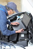 Car Mechanic with diagnostic notebook on car Royalty Free Stock Photos