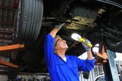 Car mechanic examining car using flashlight in auto repair service royalty free stock images