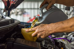 Car mechanic fills a fresh lubricant engine oil Stock Images