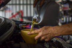 Car mechanic fills a fresh lubricant engine oil Stock Photos