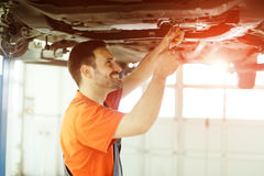 Car mechanic fixing a car. In garage at dealership Royalty Free Stock Photo