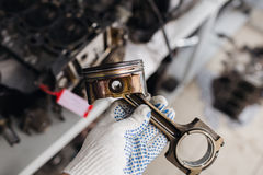 Car mechanic in garage with old car engine piston. Car mechanic in garage with old car engine piston Stock Image