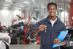 Car mechanic in garage. Young smiling car mechanic in auto repair service garage Royalty Free Stock Image