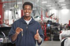 Car mechanic in garage. Young smiling car mechanic in auto repair service garage Stock Photos