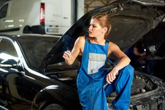 Car mechanic girl sits on open car hood and smokes. Car mechanic girl sits on an open car hood and smokes. In the other hand, she holds a wrench. Dressed in blue Royalty Free Stock Image