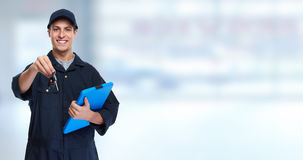 Car mechanic. Car mechanic giving auto key over blue background Stock Photo