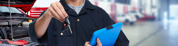 Car mechanic. Car mechanic giving auto key over garage background stock photo