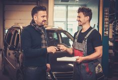 Car mechanic giving client keys to his repaired car in auto repair service. Professional car mechanic giving client keys to his repaired car in auto repair Royalty Free Stock Photos