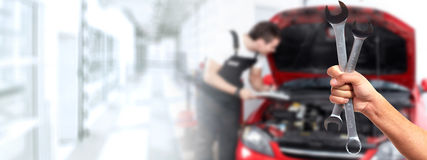 Car mechanic. Hands of car mechanic with wrench in auto repair service royalty free stock image