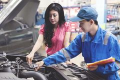 Car mechanic helping a customer fixing the car while holding a checklist.  Royalty Free Stock Images