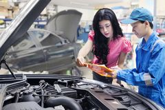 Car mechanic helps a customer standing next to the serviced car and looking through the checklist. Stock Photos