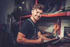Car mechanic at his workplace preparing checklist in auto repair service. Royalty Free Stock Photo