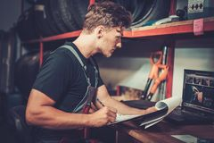 Car mechanic at his workplace preparing checklist in auto repair service. Stock Images