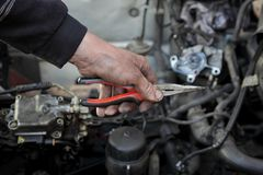 Car mechanic hold pliers tool in hand. Dirty mechanic hand  hold long nose pliers in hand with car engine in background Stock Image