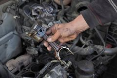 Car engine piston replacing, closeup. Car mechanic holding old piston at engine after disassembly, closeup of hand and part Royalty Free Stock Photos