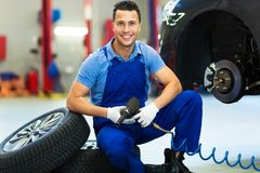 Car mechanic crouching down by a pair of wheels Royalty Free Stock Image