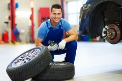 Car mechanic crouching down by a pair of wheels Royalty Free Stock Photo