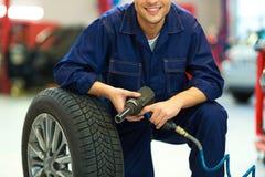 Car mechanic crouching down by a wheel Stock Photo